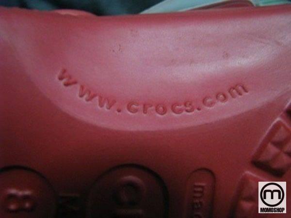 Đế giày chính hãng có một logo Crocs khác ở giữa, cùng với thông tin về kích thước, nhà sản xuất và liên kết web dẫn đến trang web chính thức của thương hiệu